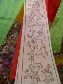 LONG HAND -- Banner with animal figures hangs among a forest of prayer flags.