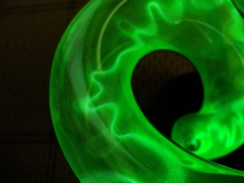 CURVE -- Plasma curves through the curving green glass tube.