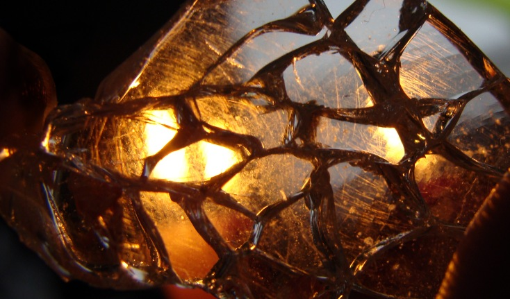 Light from the candles shines through a glass shard.