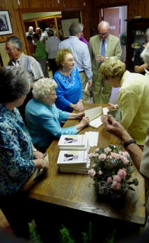 Charlotte Schexnayder (seated, center) a giant in community journalism and former state House member, signs copies of her autobiography in May 2012.