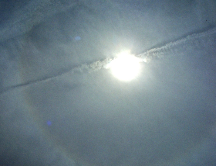 Contrail cuts across the sun's disk and the ice ring in the high clouds.