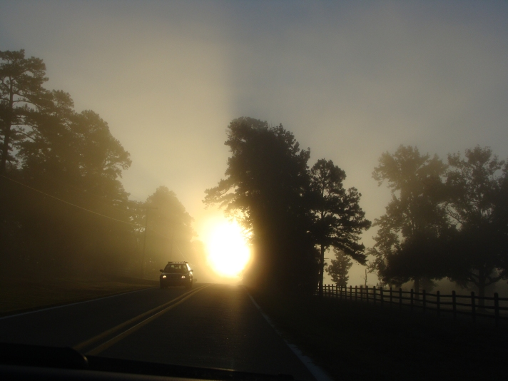 Silhouette of car in sunrise.