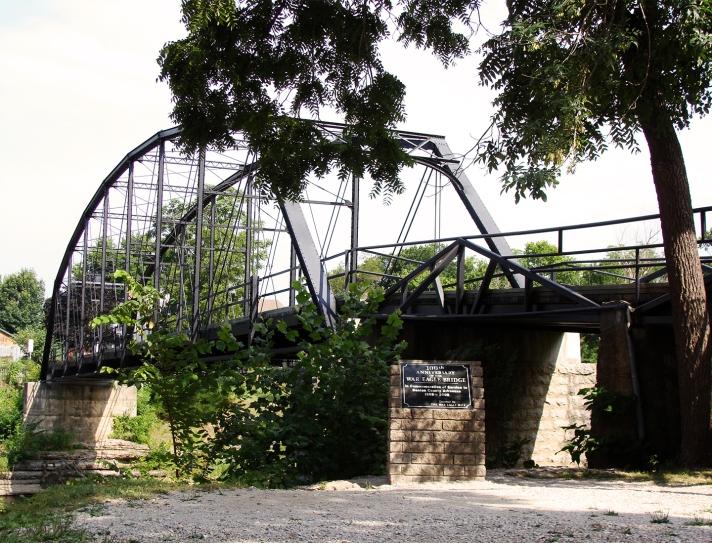 Steel span bridge over a creek.