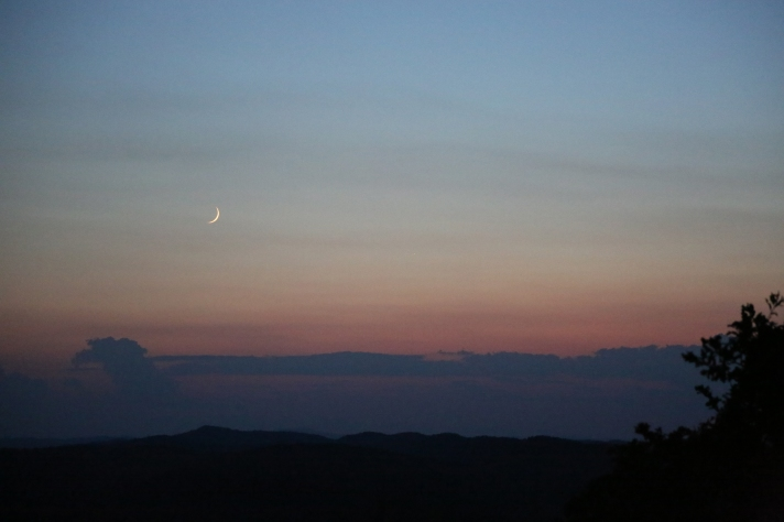Thin crescent moon in sunset.